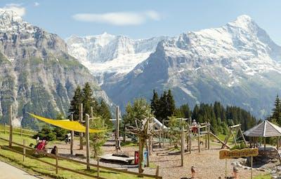 https://media.jungfrau.ch/image/upload/f_auto,fl_lossy,q_auto,c_crop,ar_16:8/c_scale,w_1320/v1479812875/fileadmin/Grindelwald_First_Sommer/Grindelwald-Alpenspielplatz-Bort-Kinder-Eiger-Sommer_.jpg
