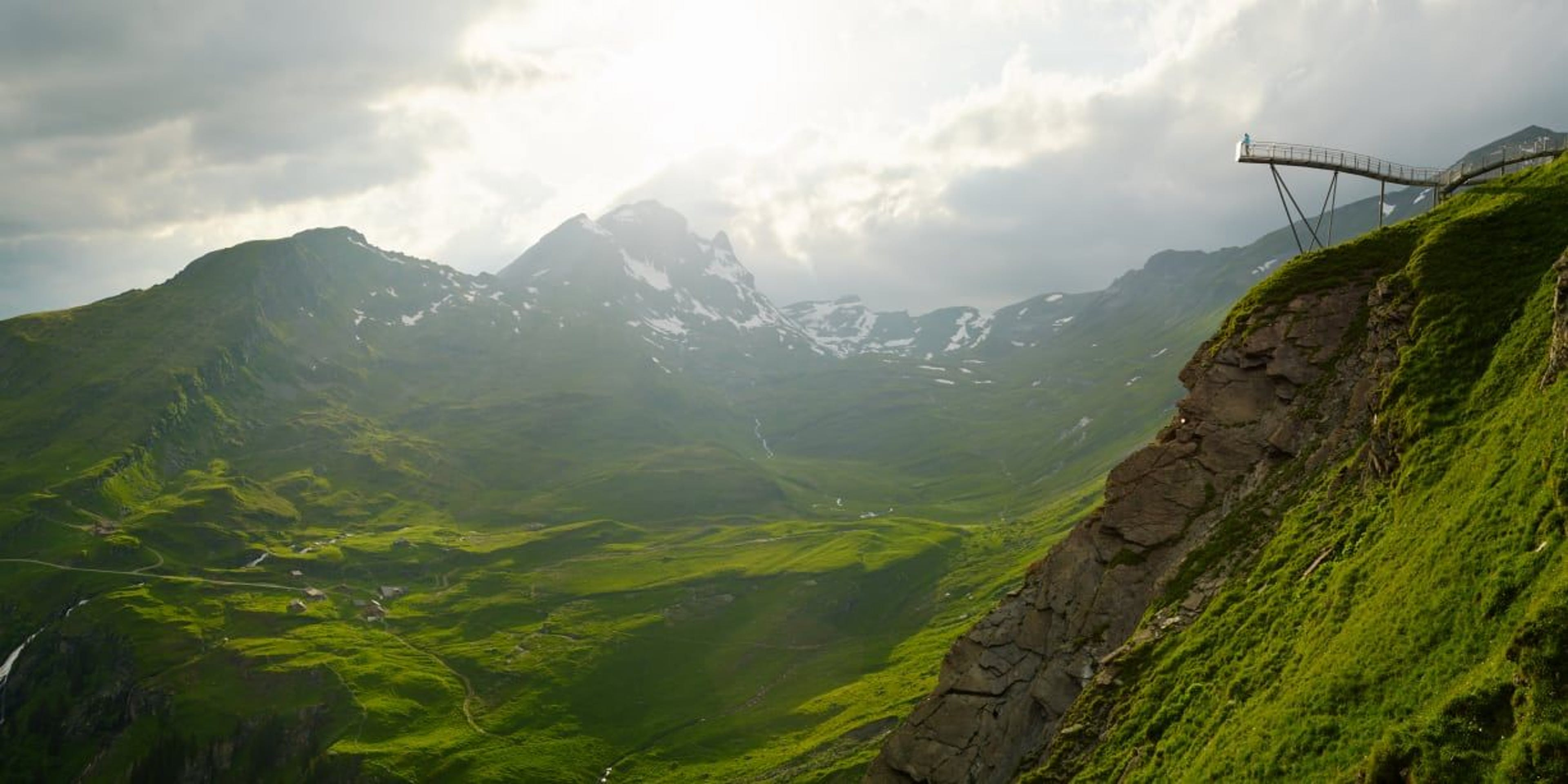 https://media.jungfrau.ch/image/upload/f_auto,fl_lossy,q_auto,c_crop,ar_16:8/c_scale,w_1228/v1479812855/fileadmin/Grindelwald_First_Sommer/Grindelwald-First-Cliff-Walk-Panorama-Alp-Bachlaeger.jpg